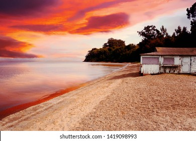 colorful view of an old house by the beach at sunset