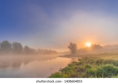 Colorful view of the river shrouded in mist creeping over the water. Orange sun slowly rising from the forest. Dawn cool morning. Grass with drops of dew and mist above the water like a haze.