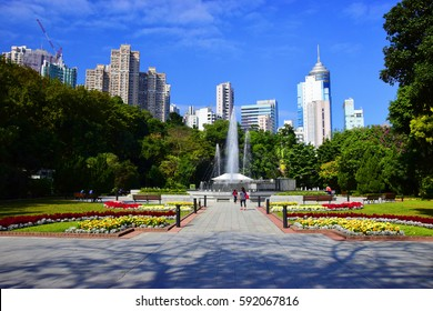 A colorful view towards the fountain and trees in the Hong Kong Zoological And Botanical Gardens.