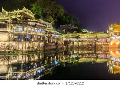 Colorful views of the Local building reflected in water of the Tuojiang River (Tuo Jiang River) in Phoenix Ancient Town (Fenghuang County), China. Fenghuang is a popular tourist destination of Asia.