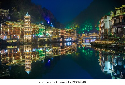 Colorful views of the Wanming Pagoda and houses reflected in water of the Tuojiang River in Phoenix Ancient Town (Fenghuang County), China. Fenghuang is a popular tourist destination of Asia.