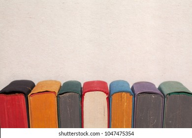 Colorful vintage books on aged textured paper background. Covers colored spines pages. macro view selective focus. copy space photo.