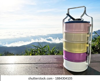 Colorful vintage food carrier placing on wooden table with beautiful view of mountain and fog