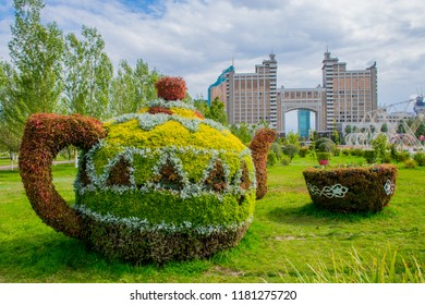 Colorful vintage pot and piala covered by grass and flowers in the green park in downtown of Astana. Cloudy summer weather in the capital of Kazakhstan.