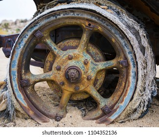 Colorful vintage wheel stuck in the desert sand rotting away.