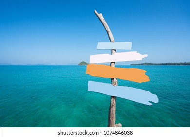 Colorful vintage wood signs on sea beach. Sea and blue sky background. Landscape and travel, or nature and sightseeing in summer concept