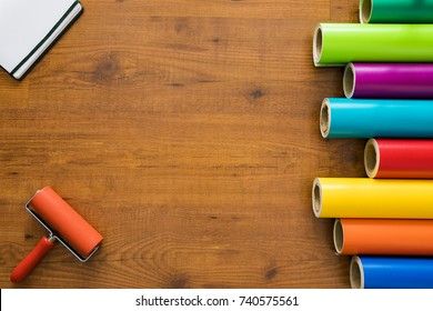 Colorful vinyl rolls on wooden background with your necessary instruments and notebook