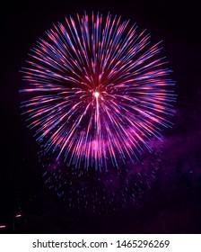 Colorful violet fireworks, one explode isolated in dark background. Malta fireworks, explode, Maltese fireworks.Pyrotechnics show. One explosion. Big ballon. Traditional maltese fireworks