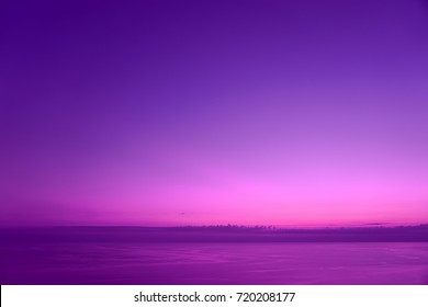 Colorful violet lilac purple sky with clouds. Calming images useful as background. Unreal colors with high saturation. Last remnants of sunlight in the sky. After sunset today over sea.