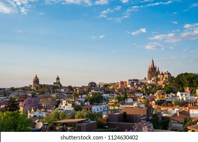 Colorful vista of San Miguel de Allende in Mexico from a high vantage point, including the church, Parroquia de San Miguel Arcangel.