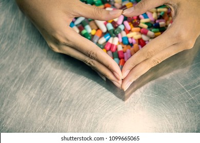 Colorful vitamin capsules pellet and tablets on metal table close up.The medicines protected from doctor hand shape like heart . Pills is dangerous when overdose.Many pills are supplementary food