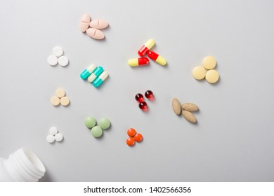 Colorful vitamin pills, capsules and medicine ampoules on an abstract background. Healthcare, medical and pharmaceutical flatlay concept. Detailed close up studio shot with copy space. Toned