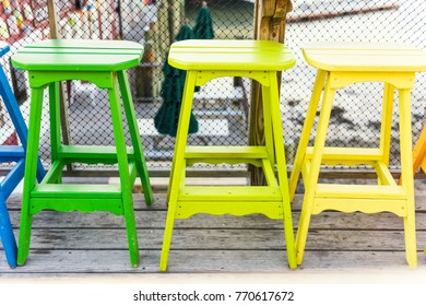Colorful vivid chairs painted green and yellow on waterfront bar restaurant