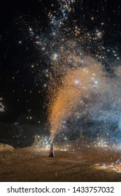 Colorful Volcano Fountain Emitting Sparks - Little Firework at Night with Dark Background. New Years Eve Celebration. Particle Effect, Glowing, Blazing, Twinkling, Glistening