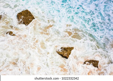 Colorful wallpaper depicting raging ocean water with rocks and foam