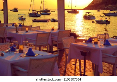 colorful warm sunset from one restaurant with tables and fantastic view on boats and seascape in Port d'Andratx in island Majorca, Spain