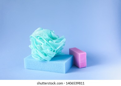 Colorful washcloths and bar of soap on a soft blue background. Accessories for body care and hygiene.