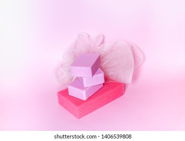 Colorful washcloths and bars of soap on a soft pink background. Accessories for body care and hygiene.
