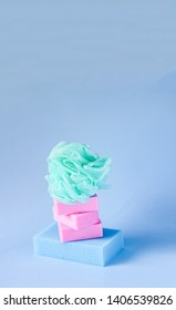 Colorful washcloths and bars of soap on a soft blue background. Accessories for body care and hygiene.