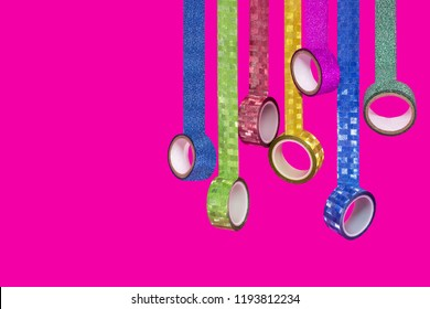 Colorful washi tapes hang loose on pink background. Washi tape rolls for handcraft. High quality sticky tape made from rice paper. Minimal color concept