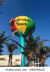 Colorful water tower in a shape of a ball surrounded by palm trees in Hallandale Beach, Florida.