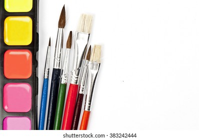 Colorful watercolor paints set with multicolored brushes isolated on white background with space for your text
