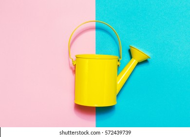 Colorful Watering Can on Colored Background. Flat Lay. Minimalistic Concept. Spring or Summer Concept.