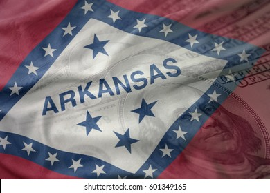 colorful waving flag of arkansas state on a american dollar money background. finance concept