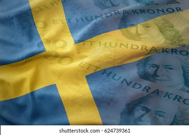 colorful waving national flag of sweden on a swedish crown money banknotes background. finance concept