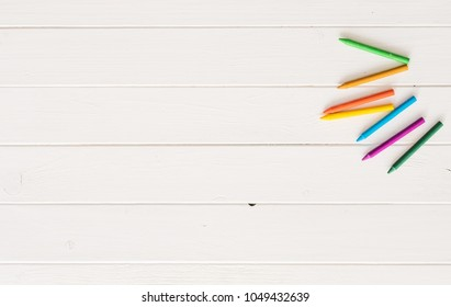 Colorful wax crayons for drawing on the white wooden table. Top view and copyspace. space for caption, empty space for text