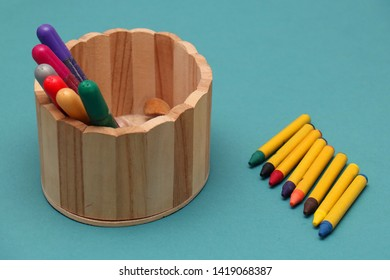 Colorful wax and sparkling crayons in wooden box on blue table