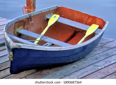 Colorful weathered rowboat painted red, white, and blue with yellow oars located on dock in coastal Maine.