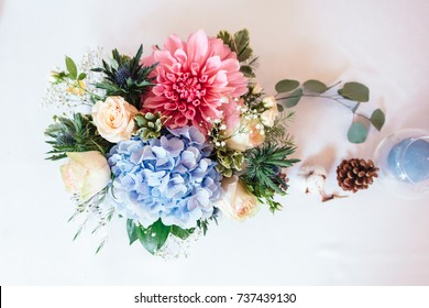 Colorful wedding reception table arrangement. Flower composition of hydrangea, roses. Wedding decor.