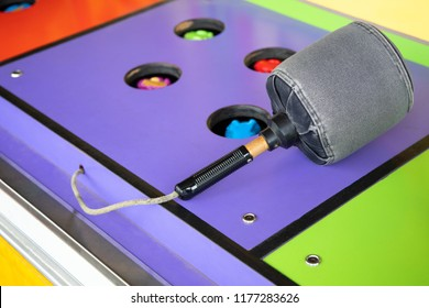 Colorful Whack a Mole game at a carnival and arcade, with padded mallet and space for text on the left
