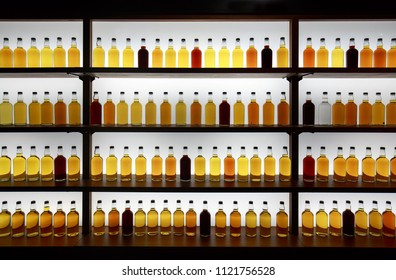 Colorful whiskey bottles on shelf against bright white light