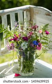 Colorful wild flower bouquet  on a white garden bench in a summer garden