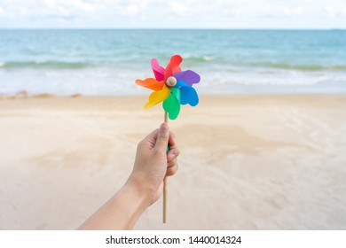 Colorful windmill paper embroidered on the beach Sea view in the daytime with a blue background. Summer concept.