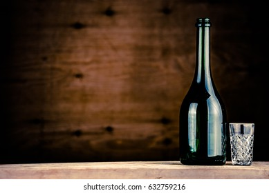 colorful wine bottle with glass on a wooden background