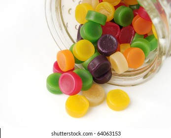 Colorful wine gum sweets falling out of glass jar.