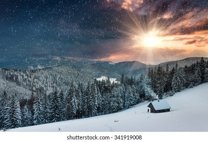 Colorful winter evening in the mountains at sunset. Dramatic overcast sky and snowing. View of the old farm and tourist near.