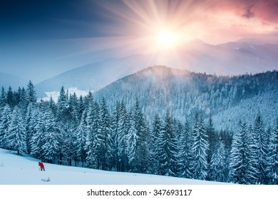 Colorful winter evening in the mountains at sunset. Dramatic overcast sky. Photographer to shoot snow tops.