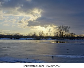 colorful winter sunset on frozen river ice with dramatic clouds