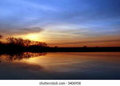 Colorful Winter Sunset and Silhouette of Riparian Oak Trees Reflected in Wildlife Pond, San Joaquin Delta, Central Valley, California