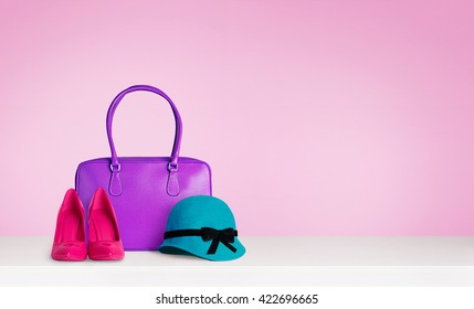 Colorful woman fashion accessories on the table isolated on pink. A purple leather bag,red heels and a blue green hat.