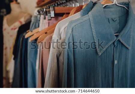 Colorful women's clothes hang on hangers in a retail shop. Fashion and shopping concept