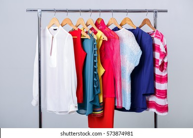 colorful womens clothes on hangers on rack on gray background. w