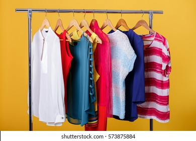 colorful womens clothes on hangers on rack on orange background.
