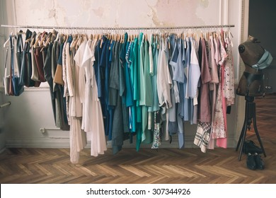 Colorful women's dresses on hangers in a retail shop. Fashion and shopping concept. Toned picture