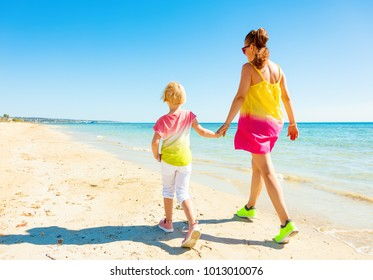 Colorful and wonderfully cheerful mood. Full length portrait of modern mother and daughter in colorful clothes on the seacoast walking