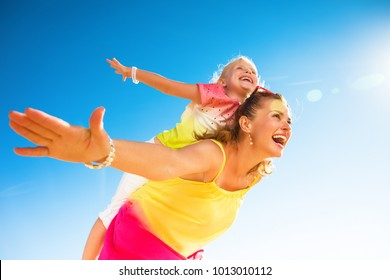 Colorful and wonderfully cheerful mood. happy trendy mother and child in colorful clothes on the seashore having fun time